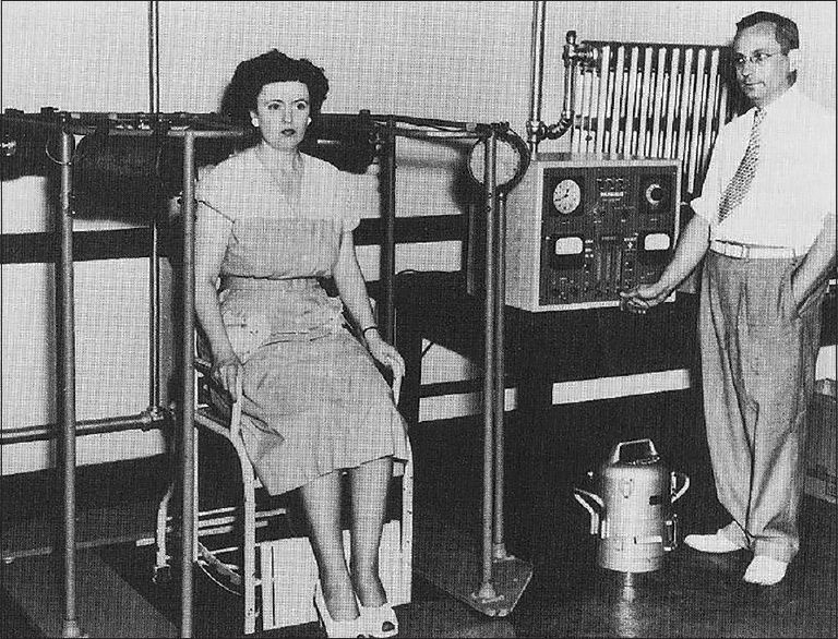 Figure 4: A volunteer shows how the multiscaler works, Dr. Saul Hertz stands next to the machine (published with permission of the Dr. Saul Hertz archive)